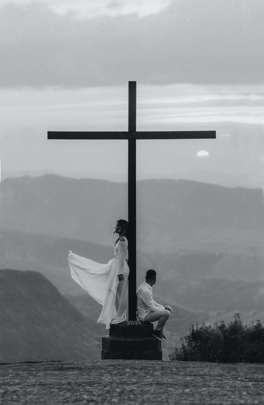 man and woman pose on a cross monument