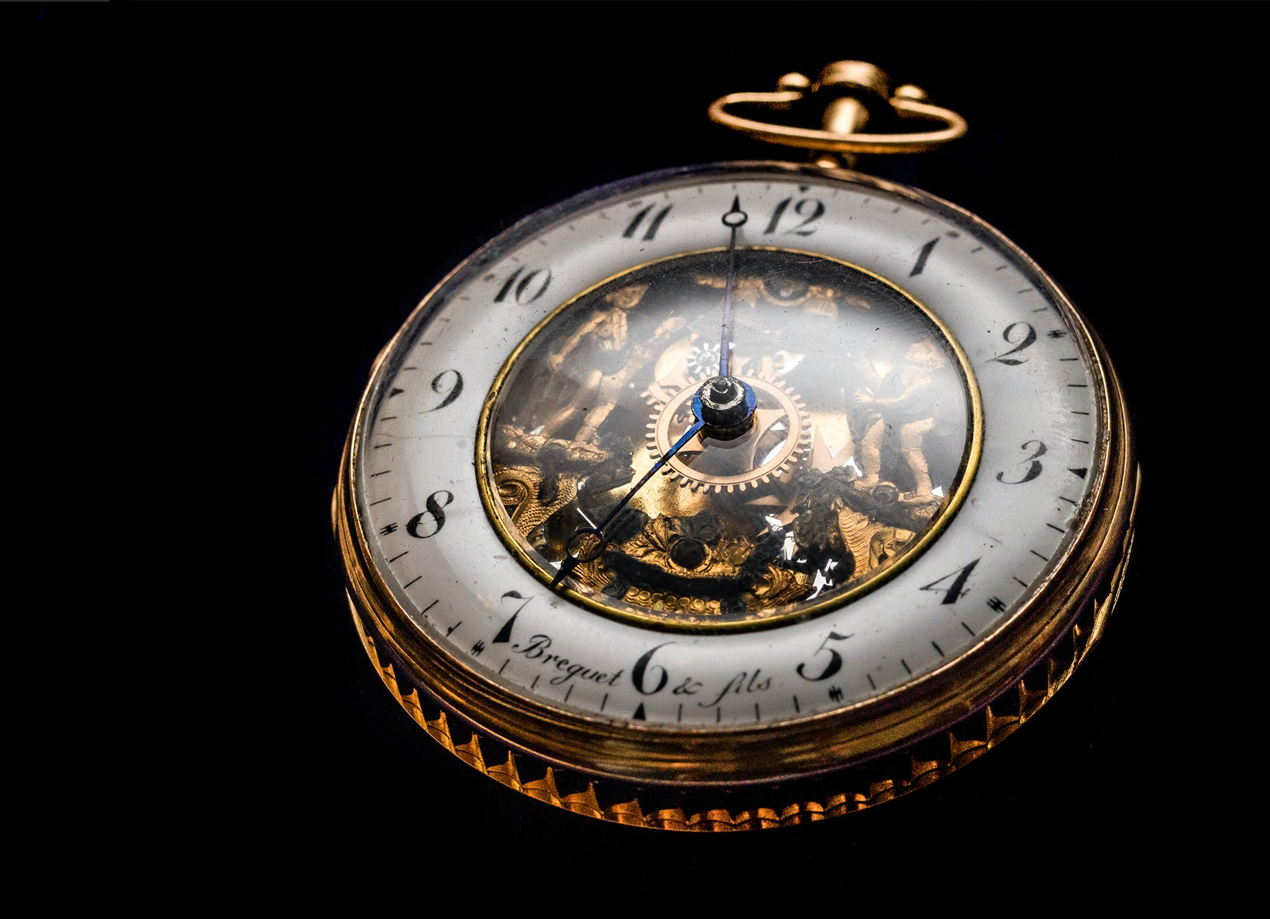 round gold colored pocket watch