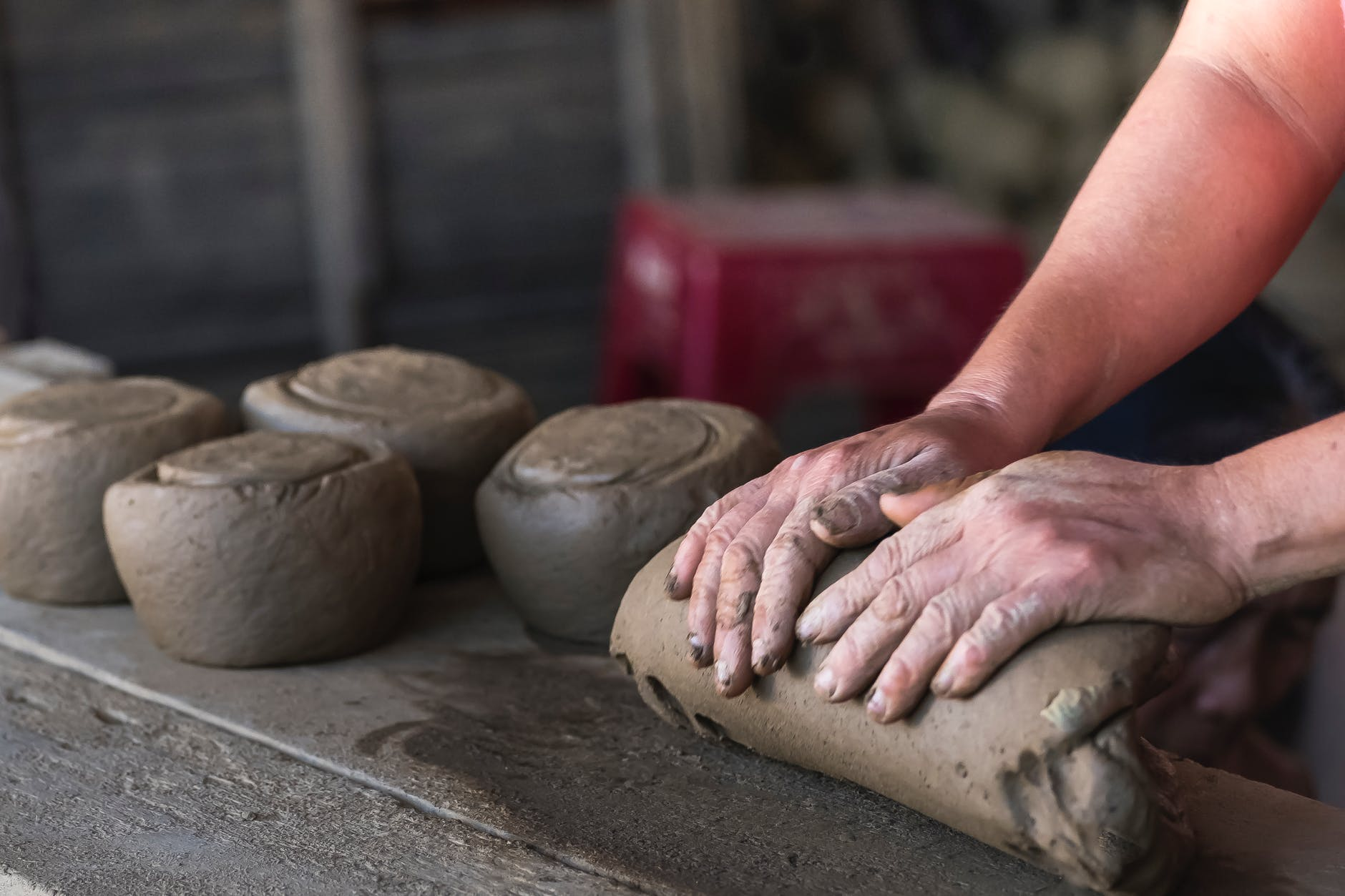 person molding brown clay